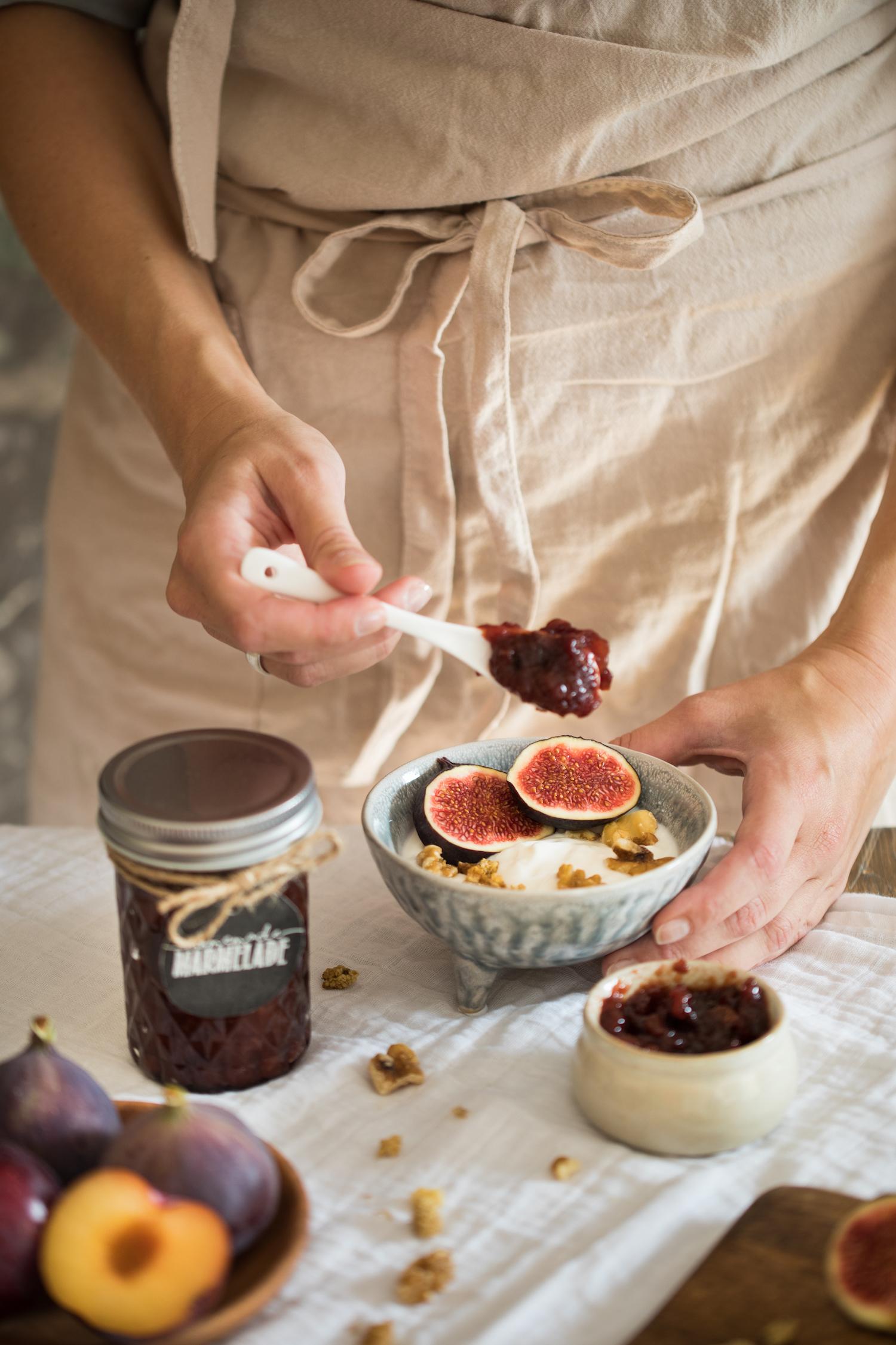 Auf eine Schale Joghurt mit Feigen wird mit einem Löffel ein Klecks Pflaumenmus aus dem Backofen gegeben.