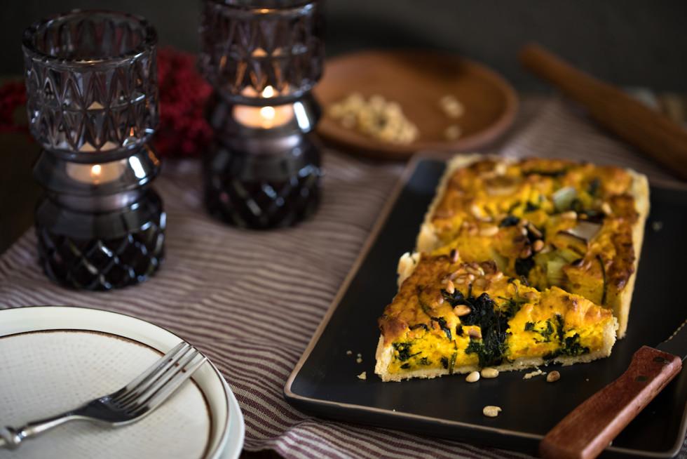 Kürbis Quiche in dreieckige Stücke geschnitten auf einem rustikalen Esstisch.