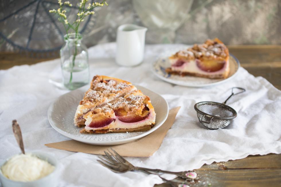Ein Stück Pflaumenkäsekuchen mit Streuseln auf einer Kaffeetafel serviert.