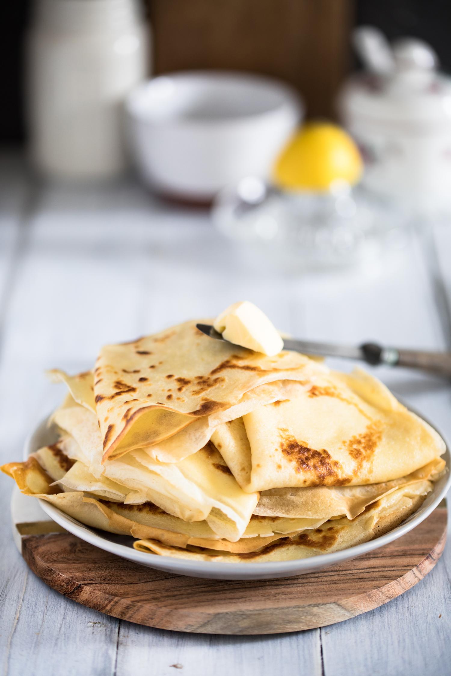 Stapel mit schwedischen Pfannkuchen, dazu Butter, Zitronensaft und Marmelade.