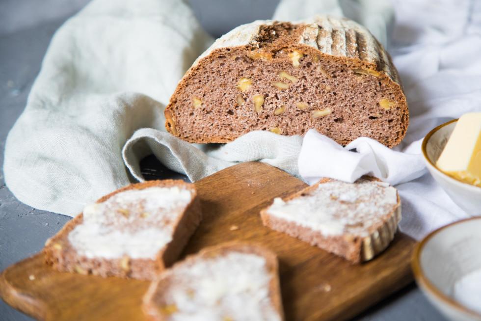 Walnussvollkornbrot im Anschnitt und Brotscheiben mit Butter beschmiert.