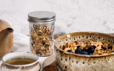 Granola Müsli im Einmachglas und als Frühstück ein einer Schale mit Porridge.