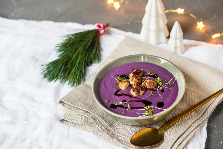 Rotkohlsuppe mit Bratwurstbällchen serviert in einer Suppenschale