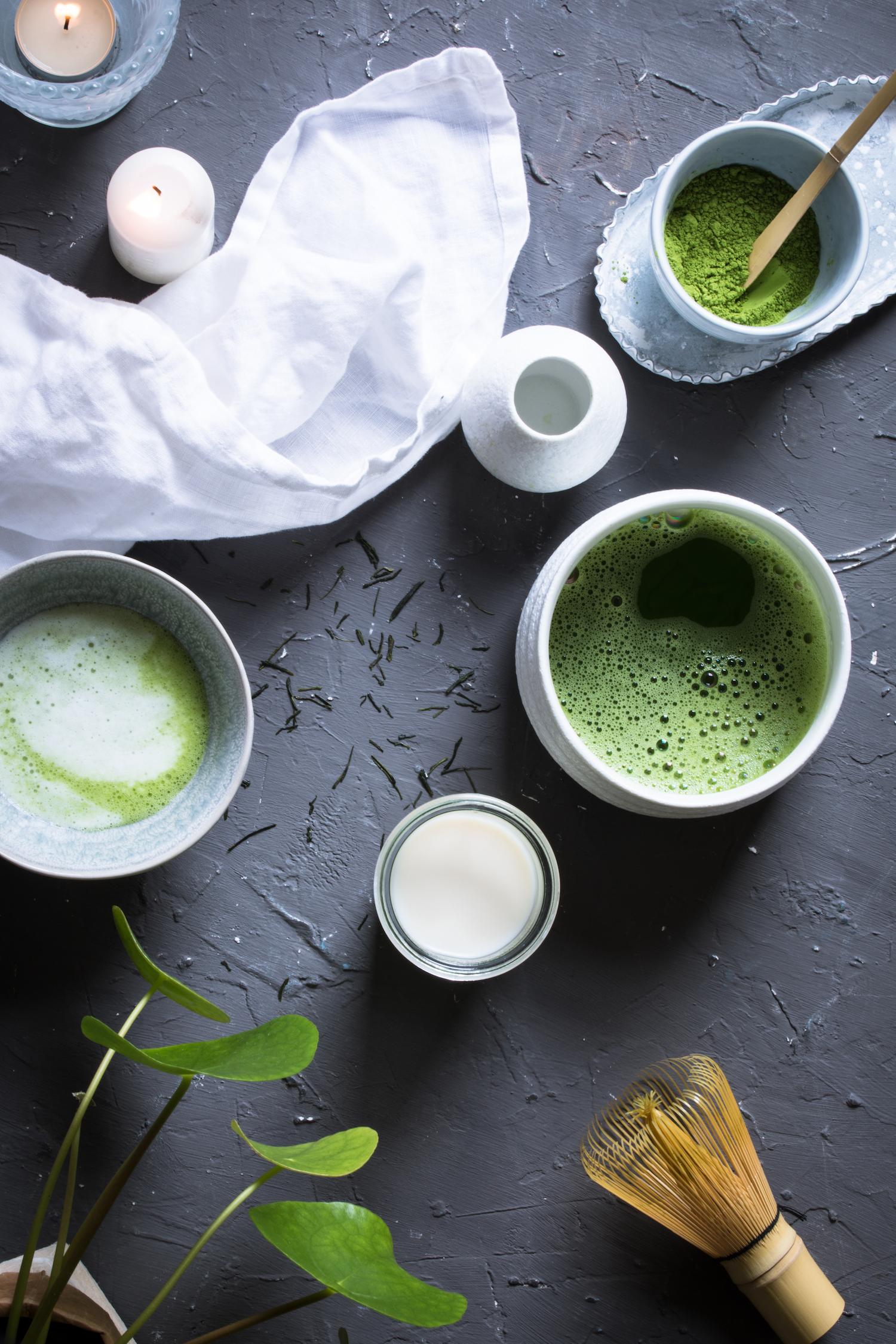 Matcha Zubereitung mit Schale, Besen und Kerzen für eine schöne Teezeremonie.