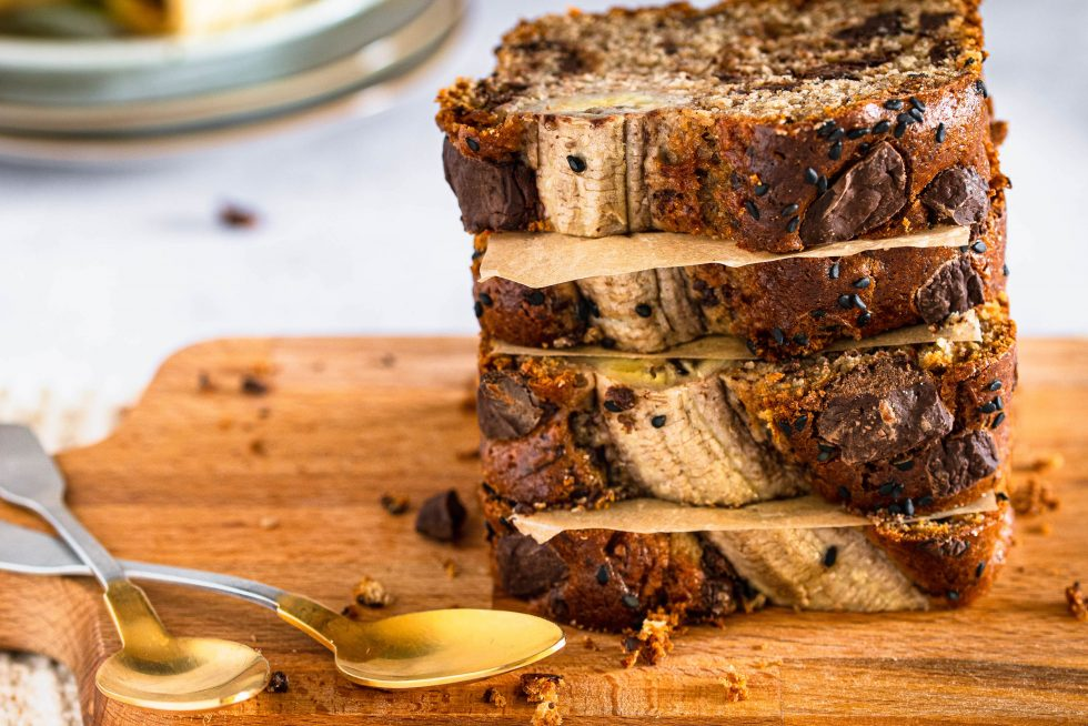 Bananenbrot mit Tahin und Schokolade in Stücke geschnitten und auf einem Holzbrett gestapelt.