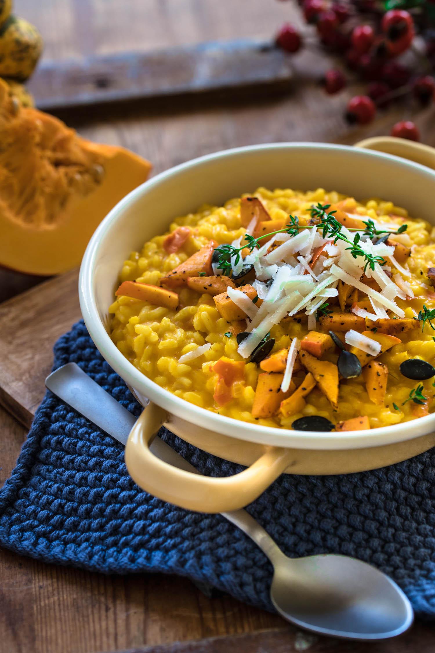 Kürbisrisotto serviert mit Kürbiswürfeln, Parmesan und Thymian.