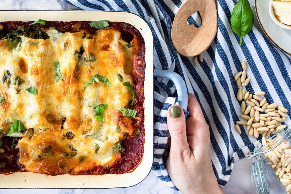Vegetarische Cannelloni mit Käse überbacken in einer hellblauen Auflaufform serviert.